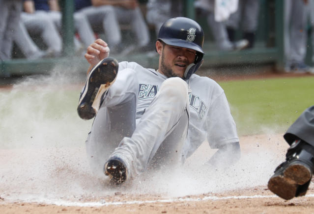Seattle Mariners' Kristopher Negron slides to score on a triple by Guillermo Heredia during the third inning of a baseball game against the Texas Rangers, Sunday, Sept. 23, 2018, in Arlington, Texas. (AP Photo/Jim Cowsert)