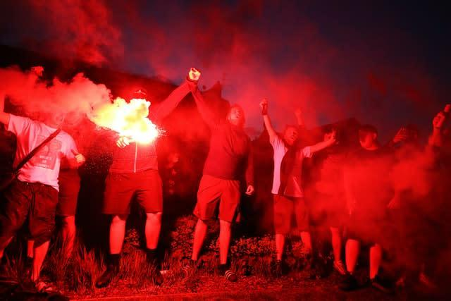 Liverpool fans let off flares outside Anfield as they celebrate Chelsea's win over Manchester City which saw them crowned champions (Martin Rickett/PA).