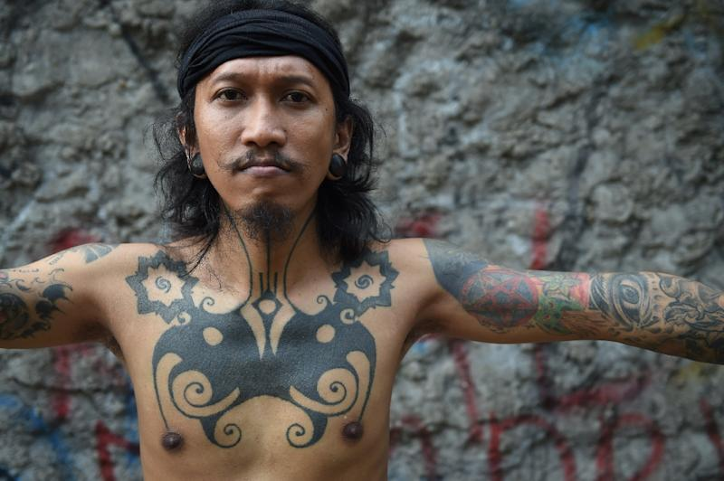 Ranu Khodir, a celebrated Jakarta tattoo artist who uses the traditional 'hand-tapping' method, displays his Dayak tribe motif tattoo at the Bau Tanah tattoo museum in Jakarta (AFP Photo/Romeo Gacad)