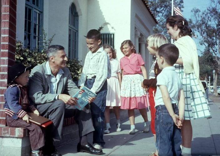 American author and illustrator Dr Seuss (Theodor Seuss Geisel, 1904 - 1991) sits outdoors talking with a group of children, holding a copy of his book, 'The Cat in the Hat', La Jolla, California, April 25, 1957. (Photo by Gene Lester/Getty Images)
