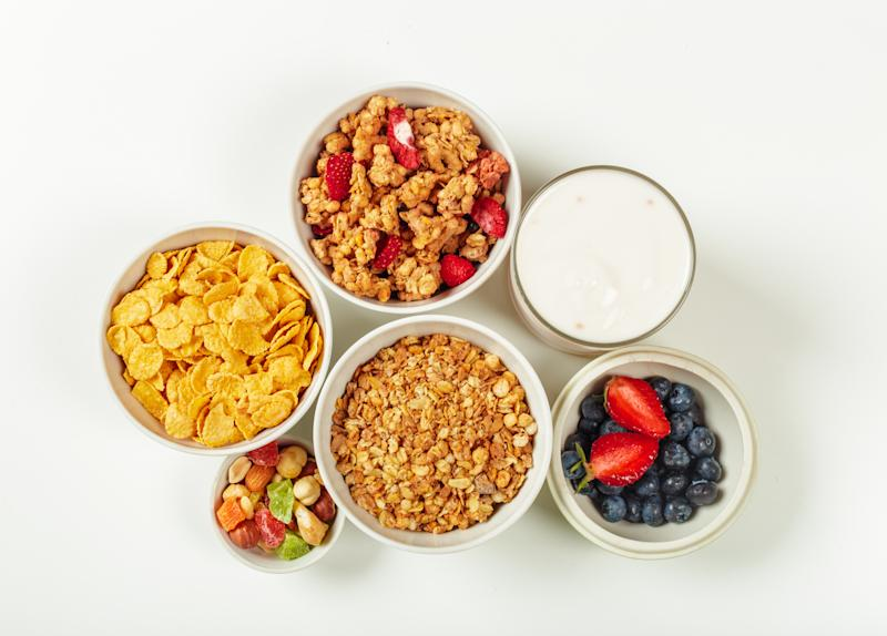 three bowls of cereal on a table with fruit