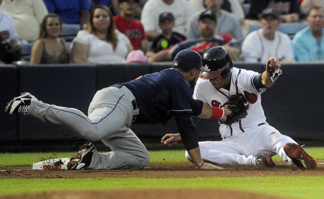 Cleveland Indians shortstop Mike Aviles, left, tags out Atlanta Braves' Andrelton Simmons who was trying to advance to third base on a Kris Medlen bunt during the third inning of a baseball game on Thursday, Aug. 29, 2013, in Atlanta. (AP Photo/John Amis)