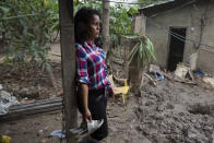 Nory Yamileth Hernandez stands at the property where she lived with 11 others, including her three teenage children, before it was flooded by last year's hurricanes Eta and Iota in San Pedro Sula, Honduras, Tuesday, Jan. 12, 2021. Hernández, 34, said she had joined the first big migrant caravan hoping to reach the U.S. in October 2018 but didn't make it to Mexico before turning back, and is sure she will try again soon. (AP Photo/Moises Castillo)