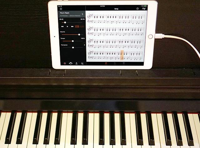 The iPad connects to the piano to display the sheet music for any song.