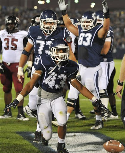 Connecticut's Lyle McCombs (43) celebrates his touchdown against Massachusetts in the first half of an NCAA college football game in East Hartford, Conn., Thursday, Aug. 30, 2012. (AP Photo/Jessica Hill)
