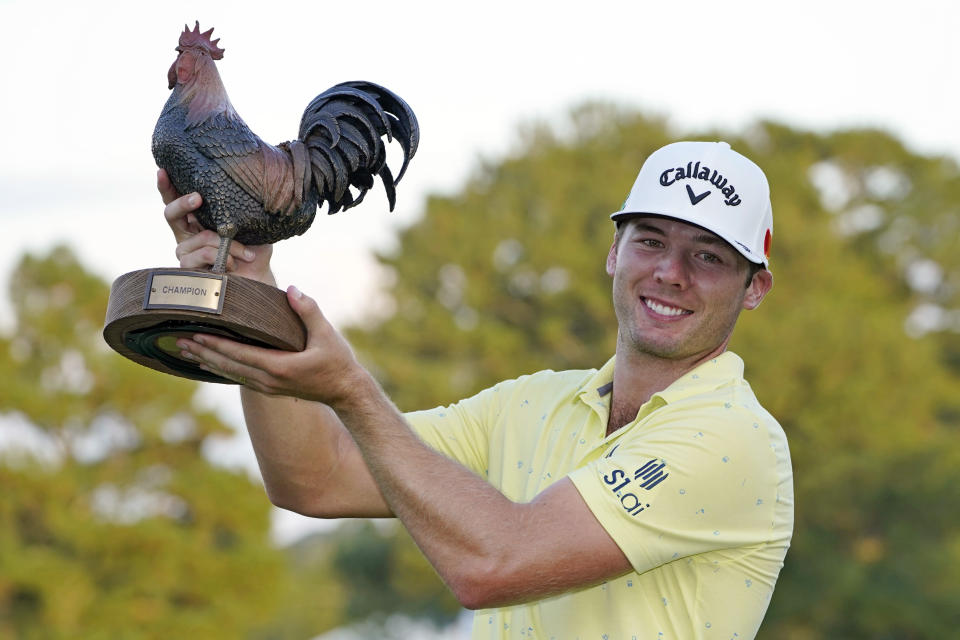 Sam Burns holds the champion's trophy after winning the Sanderson Farms Championship golf tournament in Jackson, Miss., Sunday, Oct. 3, 2021. (AP Photo/Rogelio V. Solis)