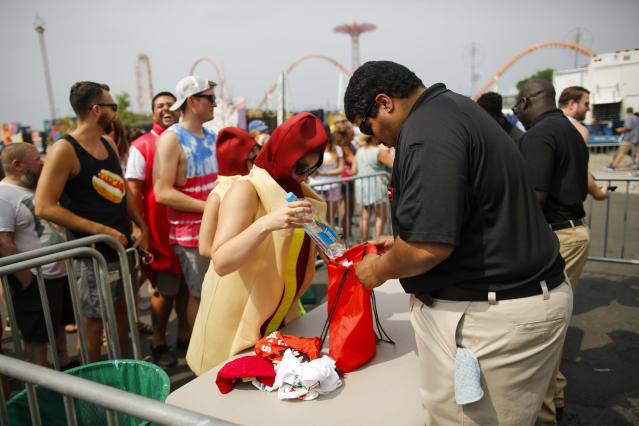 <p>A woman dressed as a hotdog is checked as she attends the Annual Nathan's Hot Dog Eating Contest on July 4, 2018 in the Coney Island neighborhood of the Brooklyn borough of New York City. In 2017 winner Joey Chestnut set a Coney Island record eating 72 hot dogs. (Photo: Eduardo Munoz Alvarez/Getty Images) </p>