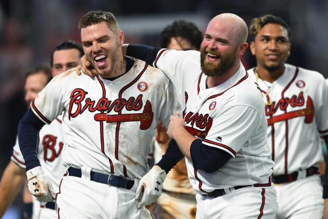 Atlanta Braves' Freddie Freeman, left, celebrates his walk-off home run with Brian McCann during the 10th inning of the team's baseball game against the Milwaukee Brewers, Saturday, May 18, 2019, in Atlanta. The Braves won 4-3. (AP Photo/John Amis)
