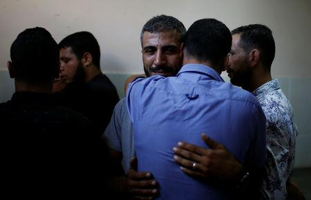 A relative of a Palestinian, who was killed in an Israeli air strike, is consoled at a hospital in the northern Gaza Strip October 17, 2018. REUTERS/Mohammed Salem