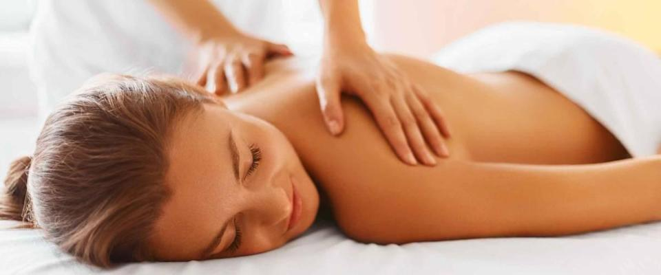 Female enjoying relaxing back massage in cosmetology spa centre. Body care, skin care, wellness, wellbeing, beauty treatment concept.