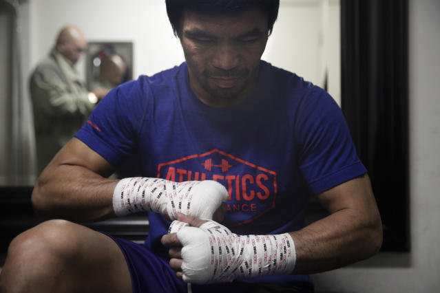Boxer Manny Pacquiao tapes his hands for a workout at the Wild Card Boxing Club Monday, Jan. 14, 2019, in Los Angeles. The Filipino legend is in the winter of his career, gearing up for what could be one big last fight. Saturday's bout versus Broner isn't it, but Pacquiao trains with the knowledge that a second megafight against Floyd Mayweather could possibly be just months away if all goes well. (AP Photo/Jae C. Hong)