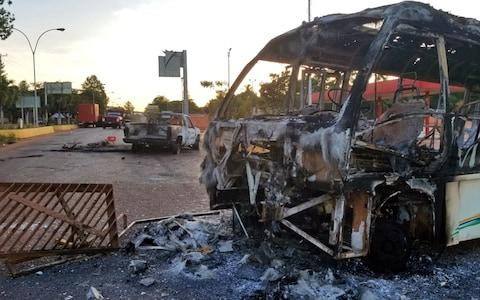 View of vehicles burnt during protests on the eve in Santa Elena de Uairen, Venezuela -in the border with Brazil - Credit: AFP