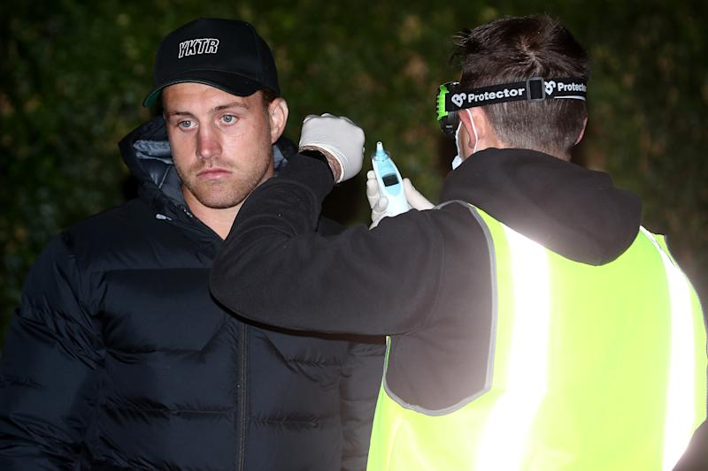Cameron Munster is pictured having his temperature checked upon arrival at an Albury hotel.