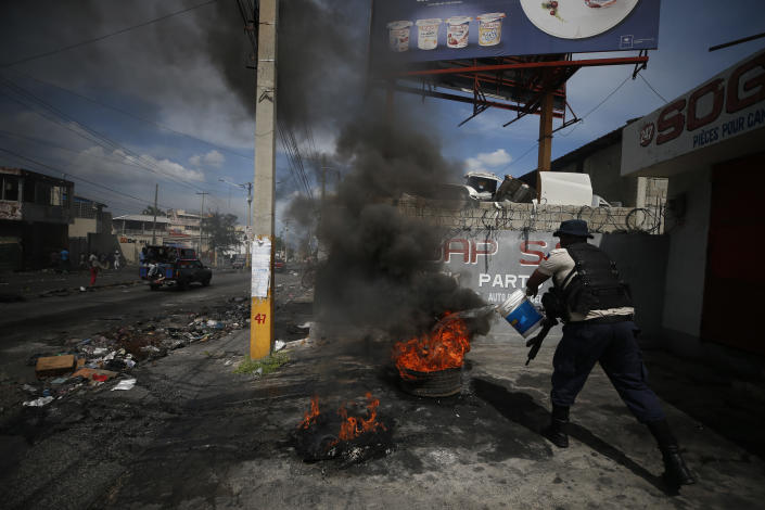 """A policeman throws water on burning tires after they were dragged out of the road to break up a barricade in Port-au-Prince, Haiti, Wednesday, Oct. 2, 2019. A group of men was protesting at the intersection after commissioning a mural of opposition organizer Jose Mano Victorieux, known as """"Badou,"""" who they said was executed Saturday night by unknown assailants.(AP Photo/Rebecca Blackwell)"""