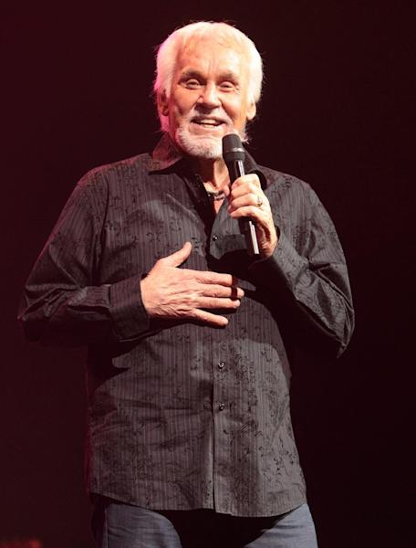 """FILE - In this March 7, 2013 file photo, singer songwriter and country music legend Kenny Rogers performs at the American Music Theatre, in Lancaster, Pa. Rogers still records and performs as the mood strikes him, but he's glad he no longer lives the life of a pop star. """"I wouldn't be out there today if you paid me,"""" Rogers joked. (Photo by Owen Sweeney/Invision/AP, File)"""