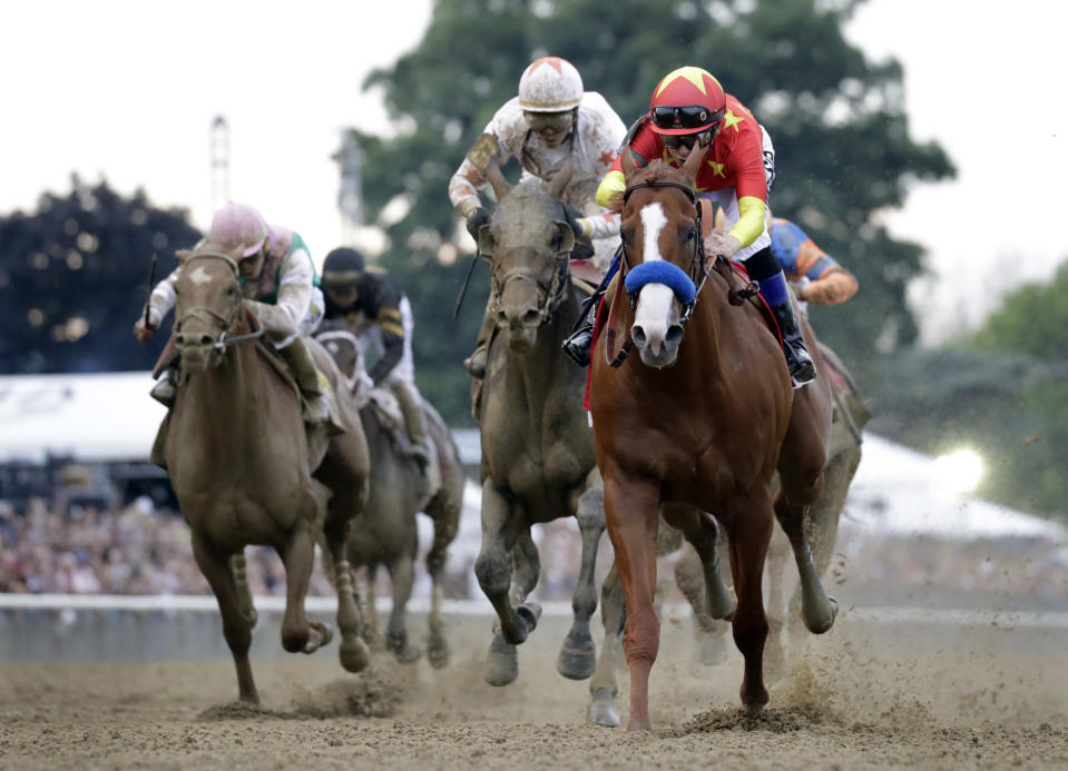 Justify, right, with jockey Mike Smith up, crosses the finish line to win the 150th running of the Belmont Stakes horse race and the Triple Crown, Saturday, June 9, 2018, in Elmont, N.Y. Gronkowski (6), with jockey Jose Ortiz up, was second. (AP Photo/Julio Cortez)