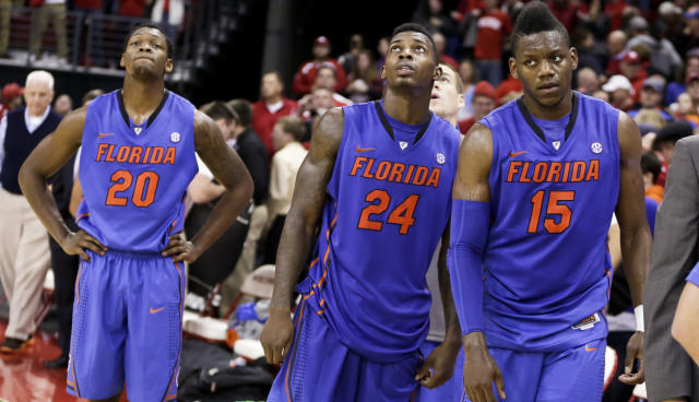Florida's Michael Frazier, left, Casey Prather (24) and Will Yeguete react after Wisconsin defeated Florida 59-53 in an NCAA college basketball game Tuesday, Nov. 12, 2013, in Madison, Wis. (AP Photo/Andy Manis)