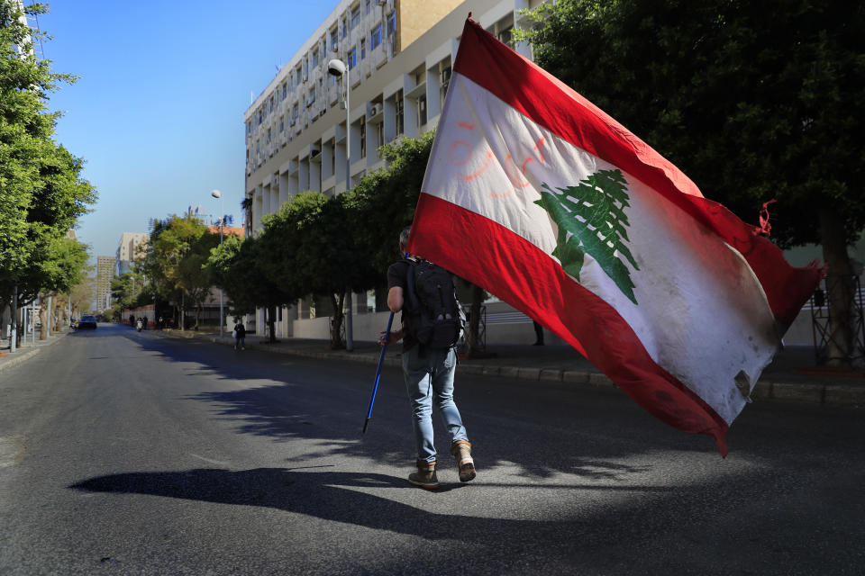 A protester holds a Lebanese flag, as he walks on a blocked main road that leads to the Central Bank during a protest against the increase in prices of consumer goods and the crash of the local currency, in Beirut, Lebanon, Tuesday, March 16, 2021. Scattered protests broke out on Tuesday in different parts of the country after the Lebanese pound hit a new record low against the dollar on the black market. (AP Photo/Hussein Malla)