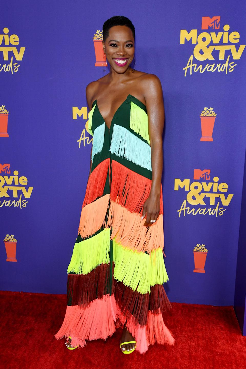 """Styled by Apuje Kalu, color-blocking was the highlight of Yvonne Orji's look. The <a href=""""https://www.teenvogue.com/story/insecure-season-4-molly-issa-friendship?mbid=synd_yahoo_rss"""" rel=""""nofollow noopener"""" target=""""_blank"""" data-ylk=""""slk:Insecure"""" class=""""link rapid-noclick-resp""""><em>Insecure</em></a> actor wore a strapless emerald Mimi Plange dress adorned with a cascade of colorful fringe. Not one to shy away from color, Yvonne rocked a bright red lip and bold neon Stuart Weissman heels to match."""
