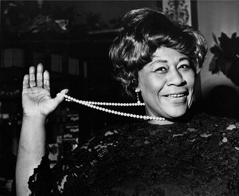 """FILE - In this Feb. 22, 1968 file photo, American jazz singer Ella Fitzgerald swings her necklace as she arrives at the Carlton Theatre in London, England. The National Portrait Gallery is putting up a photograph of Fitzgerald, often referred to as """"The First Lady of Song."""" The portrait is on view beginning Thursday, April 13, 2017, ahead of the 100th anniversary of Fitzgerald's birth. Fitzgerald, who died in 1996 at the age of 79, would have celebrated her 100th birthday April 25.  (AP Photo/Bob Dear, File)"""