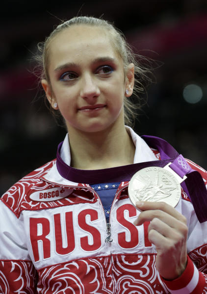 Russian gymnast Victoria Komova displays her silver medal during the artistic gymnastics women's individual all-around competition at the 2012 Summer Olympics, Thursday, Aug. 2, 2012, in London. (AP Photo/Julie Jacobson)