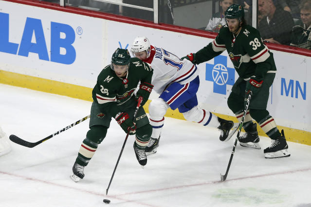 Minnesota Wild's Gabriel Dumont (28) controls the puck against Montreal Canadiens' Brett Kulak (17) in the first period of an NHL hockey game Sunday Oct. 20, 2019, in St. Paul, Minn. (AP Photo/Stacy Bengs)