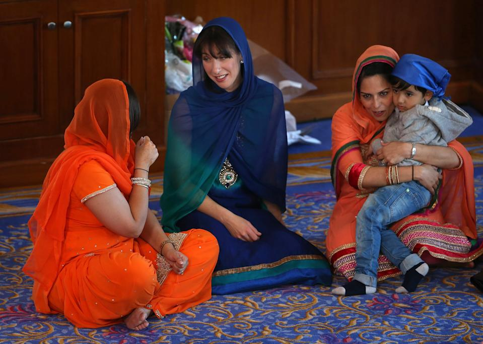 Samantha Cameron (C), wife of Britain's Prime Minister and leader of the Conservative Party, David Cameron, sits with Conservative parliamentary candidate Priti Patel (R), as she joins her husband to take part in the Sikh Vaisakhi Festival at Guru Nanak Darbar Gurdwara in Gravesend, southern England, on April 18, 2015 ahead of the general election on May 7. The Vaisakhi Festival is the most important event in the Sikh calendar and celebrates the birth Khalsa. AFP PHOTO / POOL / PETER MACDIARMID (Photo credit should read PETER MACDIARMID/AFP via Getty Images)