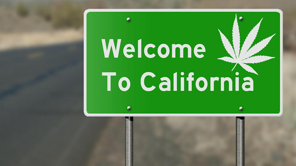 A green highway sign with white lettering that reads, Welcome to California, with a white cannabis leaf in the top right corner.