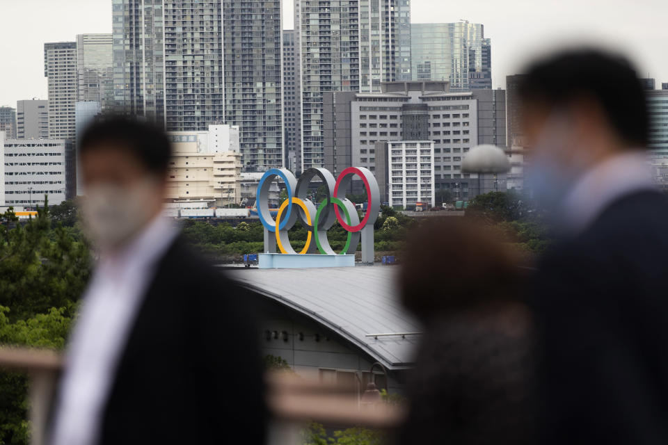 The statue of the Olympics rings overlooks people visiting a nearby shopping mall in Tokyo on Thursday, July 1, 2021. The area is closed off as it's prepared for the postponed Olympics and Paralympics Games planned to start within a month. (AP Photo/Hiro Komae)