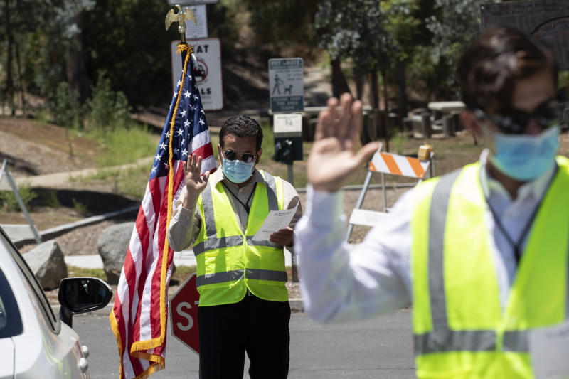 In this June 26, 2020 photo, Immigration Service Officer Bay, left, leads an oath in front of Immigration Service Officer Coronel, right, during a drive-in citizenship ceremony in El Cajon, Calif. The path to becoming a U.S. citizen, and a new voter, had already become longer under President Donald Trump when COVID-19 brought it virtually to a halt. Smaller naturalization ceremonies have resumed -- under socially distant rules that turn a once-joyous and patriotic occasion into something more like a visit to a fast-food restaurant -- but could soon stall again as the nation's citizenship agency faces an unprecedented budget shortfall and the possibility of a furlough for nearly three-fourths of its workforce. (AP Photo/Gregory Bull)