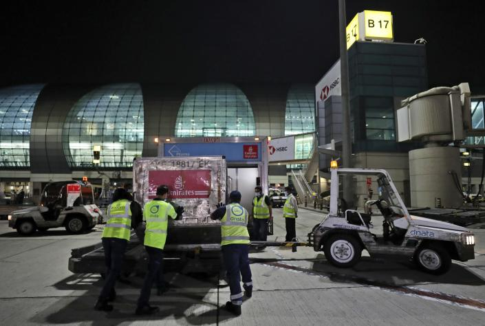 A shipment of Pfizer-BioNTech COVID-19 coronavirus vaccines is offloaded from an Emirates Airlines Boing 777 that arrived from Brussels to Dubai International Airport in Dubai, United Arab Emirates, Saturday, Feb. 20, 2021. As the coronavirus pandemic continues to clobber the aviation industry, Emirates Airlines, the Middle East's biggest airline, is seeking to play a vital role in the global vaccine delivery effort. (AP Photo/Kamran Jebreili)