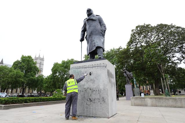 A worker cleans graffiti from the plinth of the statue of Sir Winston Churchill. (PA Images)