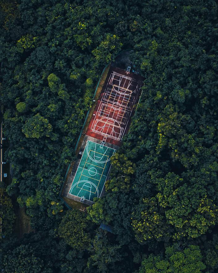 'Hoops in the woods' by @i.ride.to.drone shows basketball courts in the middle of the forest in the city-state  of Singapore.