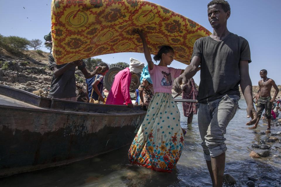 Refugees who fled the conflict in Ethiopia's Tigray region carry their belongings off a boat after arriving on the banks of the Tekeze River on the Sudan-Ethiopia border, in Hamdayet, eastern Sudan, Saturday, Nov. 21, 2020. (AP Photo/Nariman El-Mofty)
