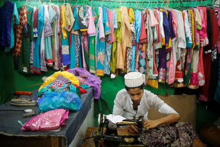 FILE PHOTO: A tailor sews a dress before he breaks fast on the first day of the holy month of Ramadan in Old Dhaka