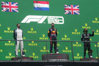 First place Red Bull driver Max Verstappen of the Netherlands, center, second place Williams driver George Russell of Britain, left, and third place Mercedes driver Lewis Hamilton of Britain, right, stand on the podium after the Formula One Grand Prix at the Spa-Francorchamps racetrack in Spa, Belgium, Sunday, Aug. 29, 2021. The race was red flagged due to weather conditions. (AP Photo/Francisco Seco)