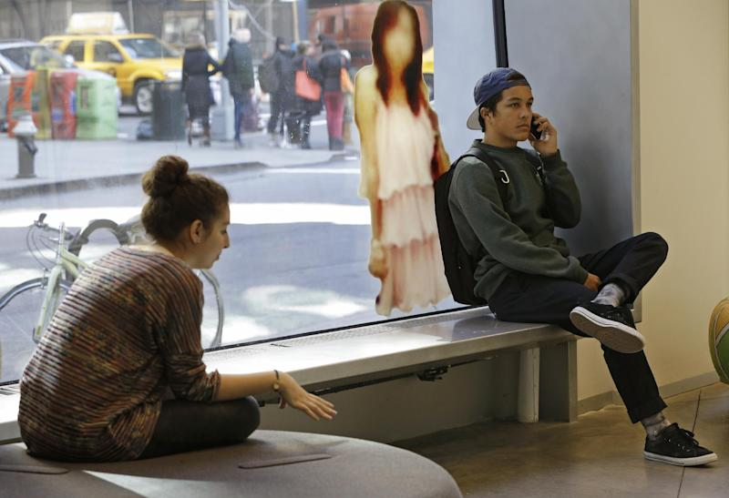 "In this Tuesday, March 5, 2013, photo, Students relax beside an image of a young woman taken from ""Google Maps,""as part of ""The Public Private"" exhibit at the Anna-Maria and Stephen Kellen Gallery in the Sheila C. Johnson Design Center at Parsons The New School for Design, in New York. The exhibit seeks to explore the boundaries and gray areas of online privacy, surveillance and data collection in the age of Facebook and Google. (AP Photo/Kathy Willens)"