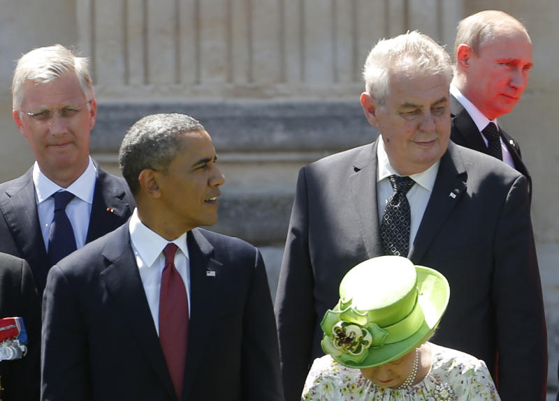U.S. President Barack Obama watches as Russian President Vladimir Putin walks to his position before a group photo as they take part in the 70th anniversary of D-Day in Benouville in Normandy, France, Friday, June 6, 2014. (AP Photo/Charles Dharapak)