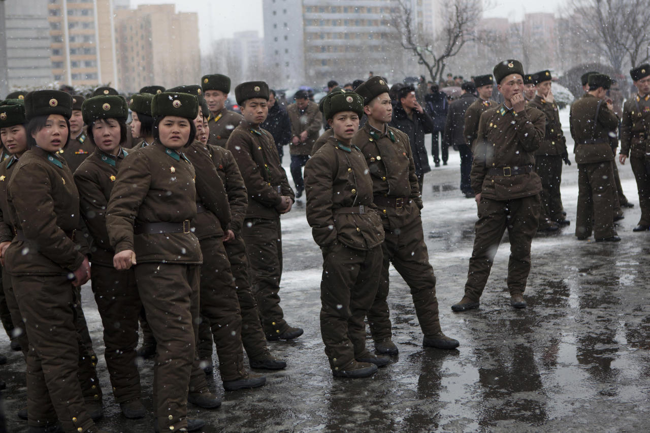 North Korean soldiers gather along a Pyongyang street during heavy snowfall on Sunday, Feb. 17, 2013. (AP Photo/David Guttenfelder)