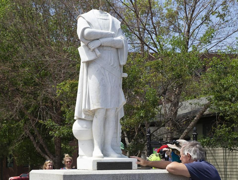A city employee inspects the decapitated statue of Christopher Columbus in Boston