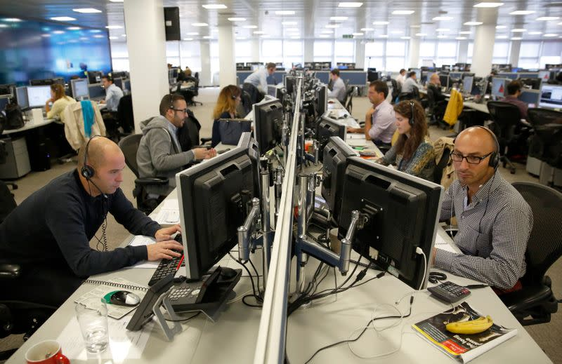 Traders sit at their desks at IG Index in London