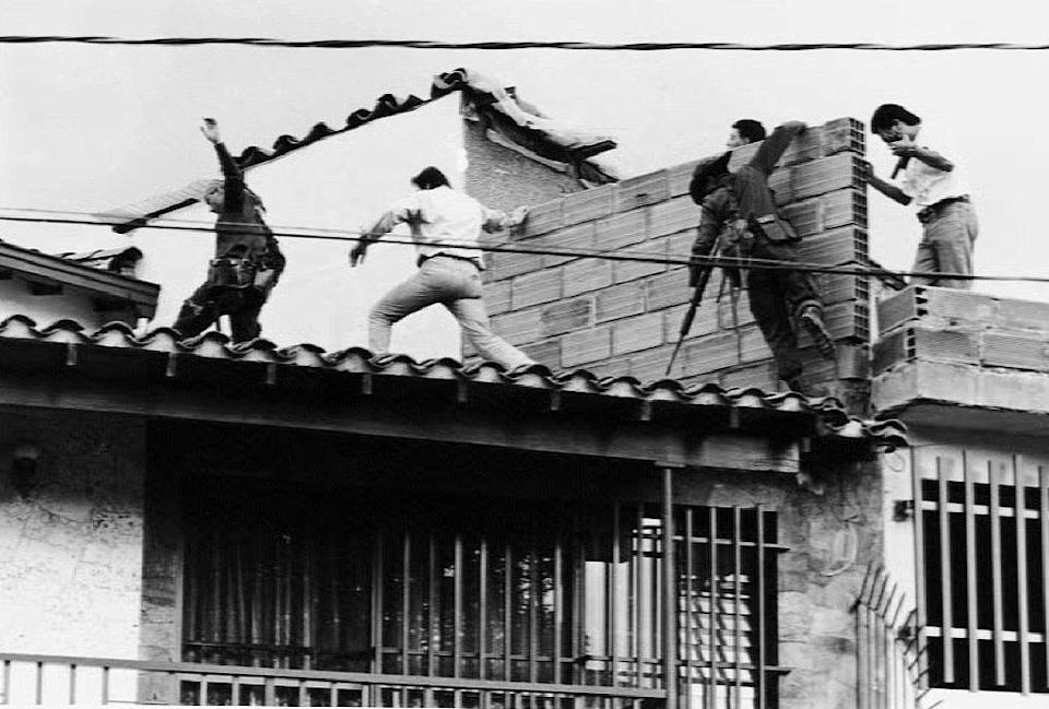 Colombian police and military forces storm the rooftop where drug lord Pablo Escobar was shot dead just moments earlier during an exchange of gunfire between security forces and Escobar and his bodyguard 02 December 1993. The death of Escobar and the bodygaurd ends a 16-month hunt for Escobar, who controlled one of the world's most ruthless drug trafficking empires. (Photo credit should read JESUS ABAD-EL COLOMBIANO/AFP via Getty Images)
