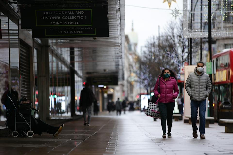 People wearing face masks walk past temporarily-closed stores on Oxford Street in London, England, on December 21, 2020. London spent its second day of what could be months under newly-introduced 'Tier 4' coronavirus restrictions today. Under Tier 4 rules non-essential shops and many other businesses including gyms and hairdressers must close, with people instructed to stay at home other than for exempted circumstances including travel to work or education. Indoor mixing between those in different households is also banned under the new tier, upending Christmas plans for a huge swathe of the population. Concern over a more infectious strain of the coronavirus in the UK has meanwhile seen dozens of countries ban arrivals from Britain, with food supplies also disrupted after France closed the cross-Channel freight route from Dover. (Photo by David Cliff/NurPhoto via Getty Images)