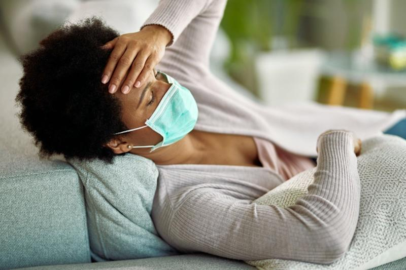 Tired black woman with face mask having a headache while lying down on sofa at home.