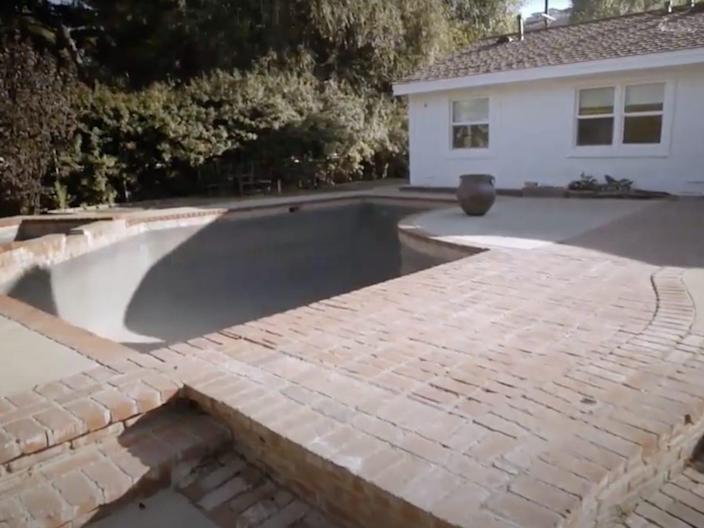 A concrete patio with an empty pool.