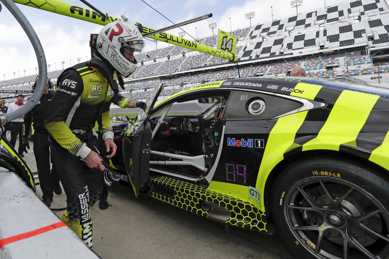 Kyle Busch climbs in his car for a turn to drive during testing for the upcoming Rolex 24 hour auto race at Daytona International Speedway, Friday, Jan. 3, 2020, in Daytona Beach, Fla. (AP Photo/John Raoux)