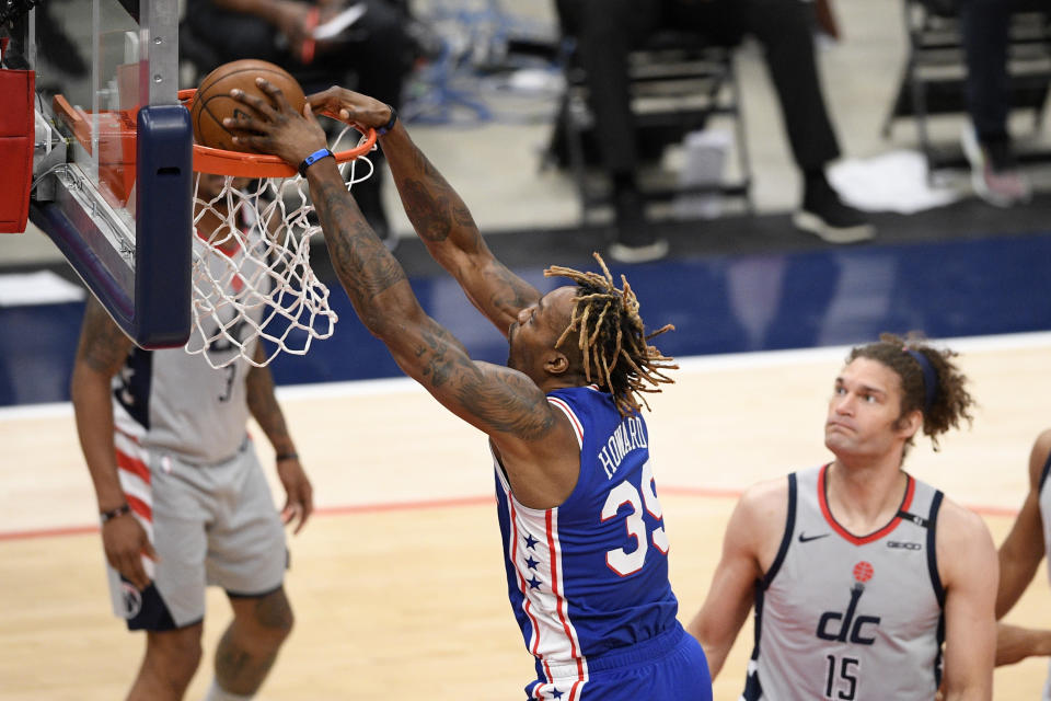 Philadelphia 76ers center Dwight Howard (39) dunks past Washington Wizards center Robin Lopez (15) during the second half of Game 3 in a first-round NBA basketball playoff series, Saturday, May 29, 2021, in Washington. (AP Photo/Nick Wass)