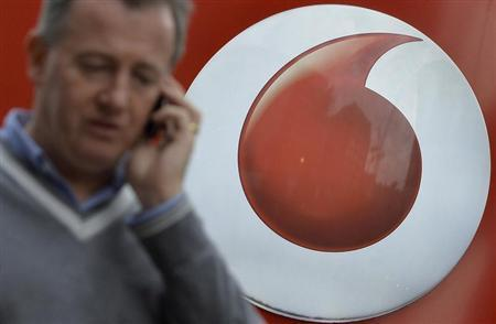 A man speaks on a mobile phone as he walks past Vodafone branding outside a retail store in London