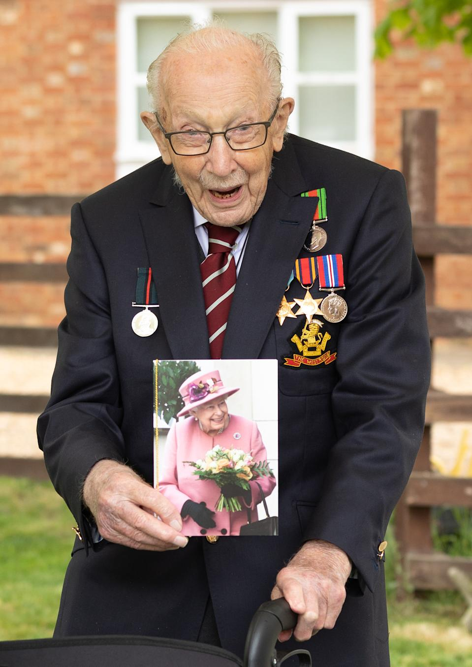 Handout photo of Second World War veteran Captain Tom Moore holding a birthday card from Queen Elizabeth II as he celebrates his 100th birthday.