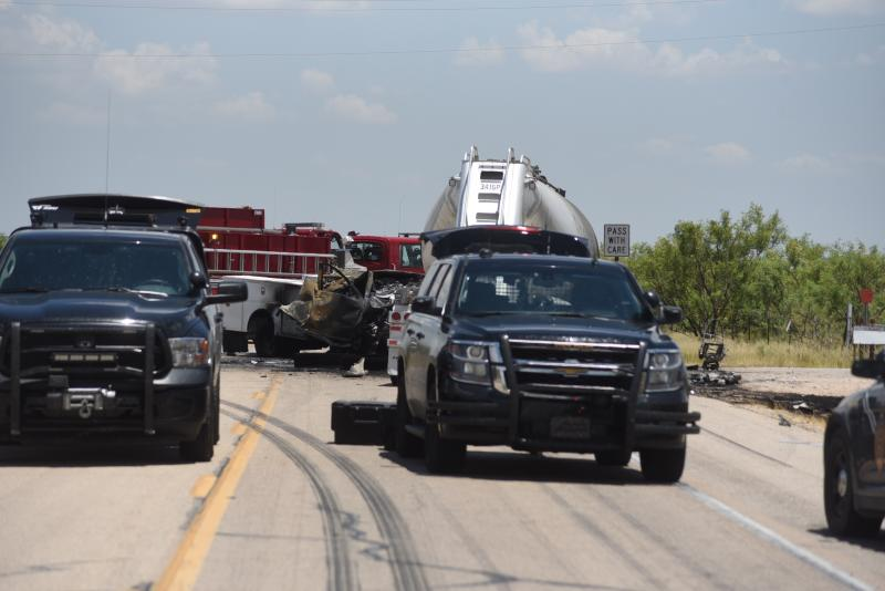 New Mexico State Police respond to a fatal crash involving a pickup truck and a semi truck along State Route 128 near Jal, New Mexico, on Thursday, July 11, 2019. Authorities say four oilfield workers traveling in the truck and the driver of the rig were pronounced dead at the scene.(Jason Farmer/The Hobbs Daily News-Sun via AP)